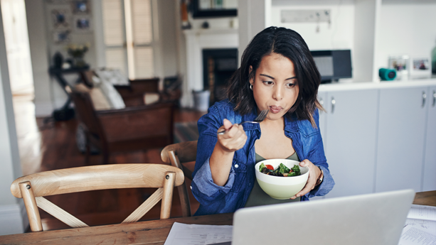 A young woman using a laptop and having a salad while working from home