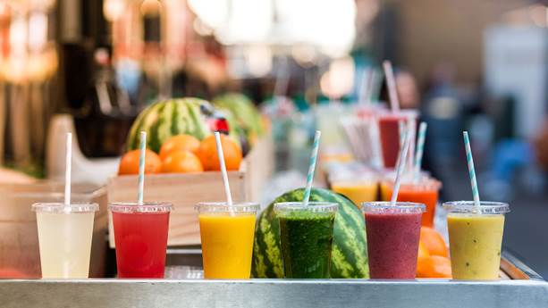 Six clear plastic cups full of colourful juices sit in front of various fruits.
