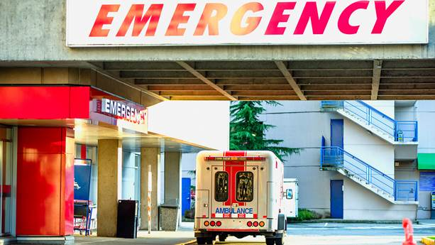 A modern ambulance car parked near the emergency entrance to the hospital in the daytime.