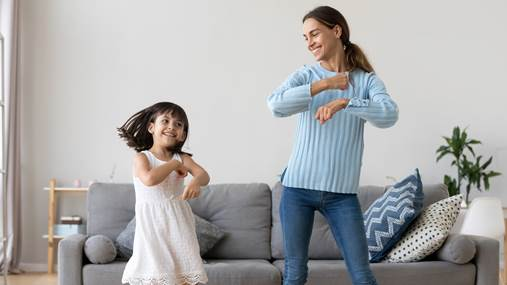 A mother and her daughter dance in their living room