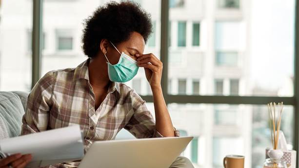 """""""African american woman with face mask having a headache while going through paperwork and using laptop while working at home. """""""