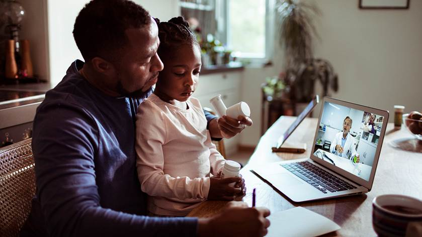 A father with his daughter on his lap attending a virtual doctor's appointment.