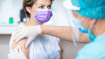 A female patient wears a protective face mask while waiting for vaccination with a doctor in surgical gloves disinfecting her arm.