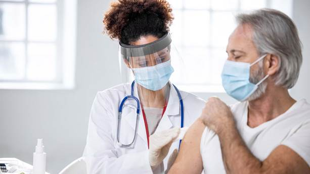 Health worker administers a flu shot to a person.