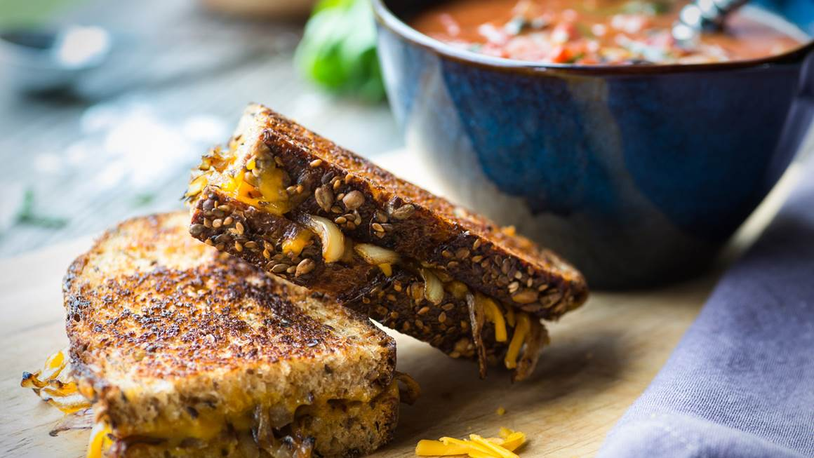 Fresh tomato soup with grilled onion and cheese sandwich on a wooden cutting board.