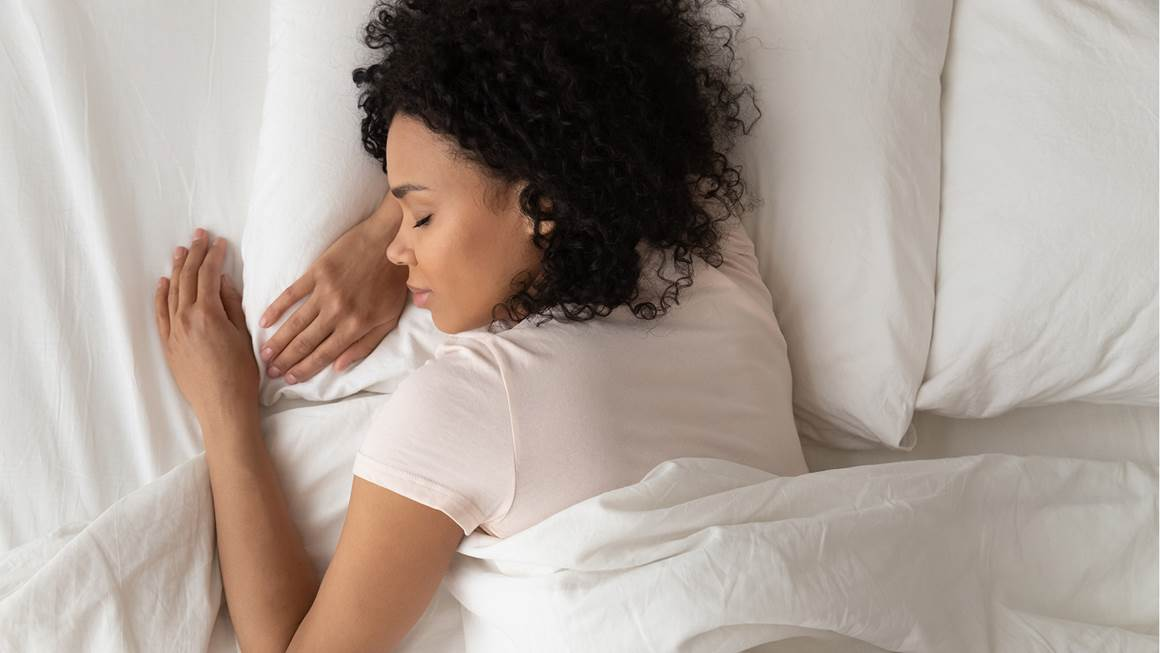 Serene young african american girl sleeping well in a comfortable bed on soft pillow white linen orthopedic mattress,  top view