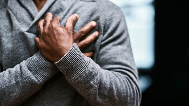 A man in a grey sweater crossing his hands over his heart.