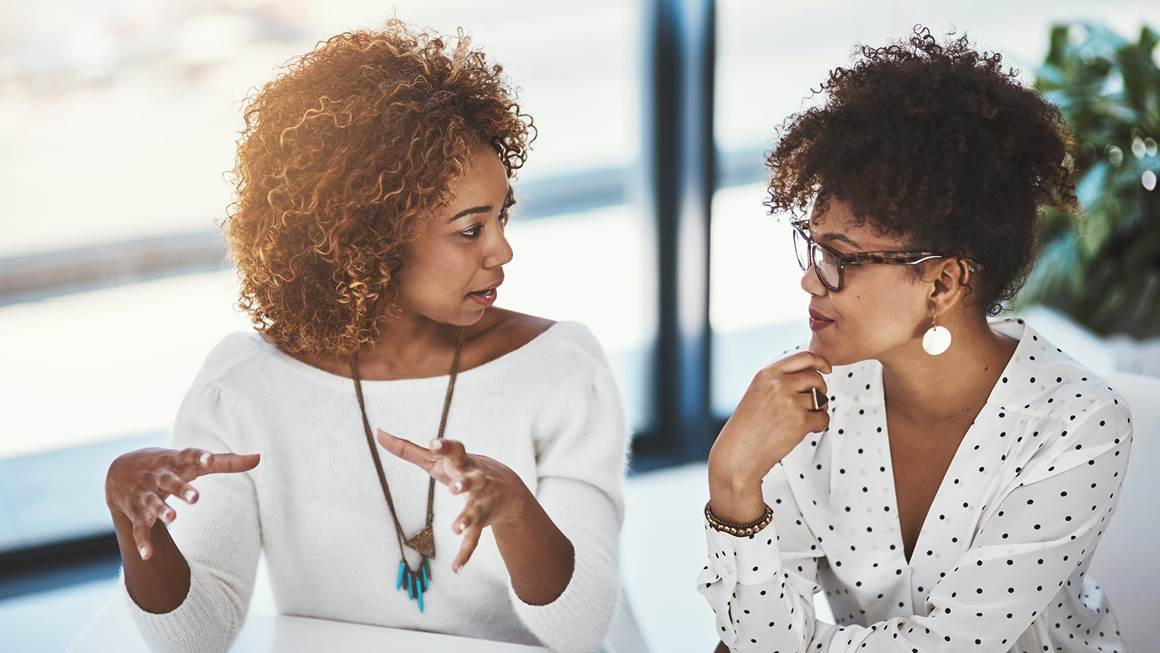 Two professional women talking to one another sitting in a boardroom