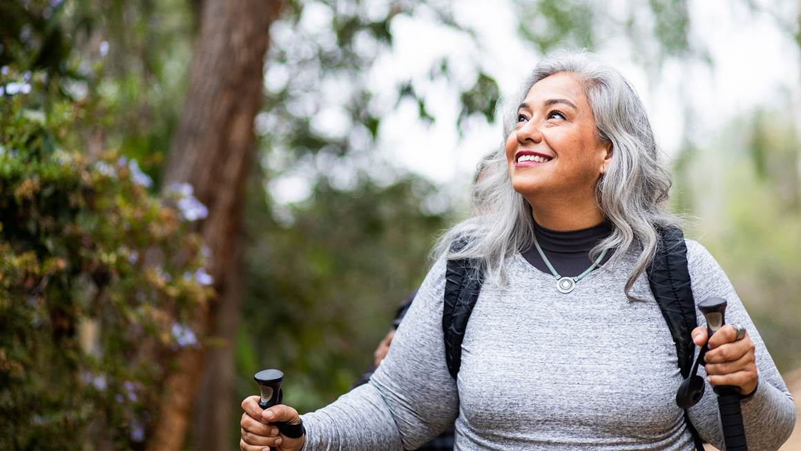 Smiling woman walking out doors holding hiking poles