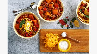 Bean, sweet potato and garlic stew in a red serving dish with bowls alongside