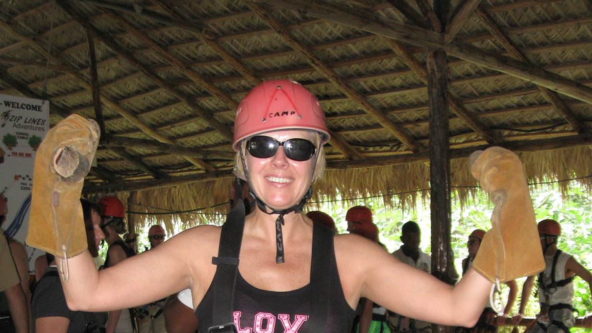 Beth Luhowy smiles wearing a pink helmet and a zipline harness.
