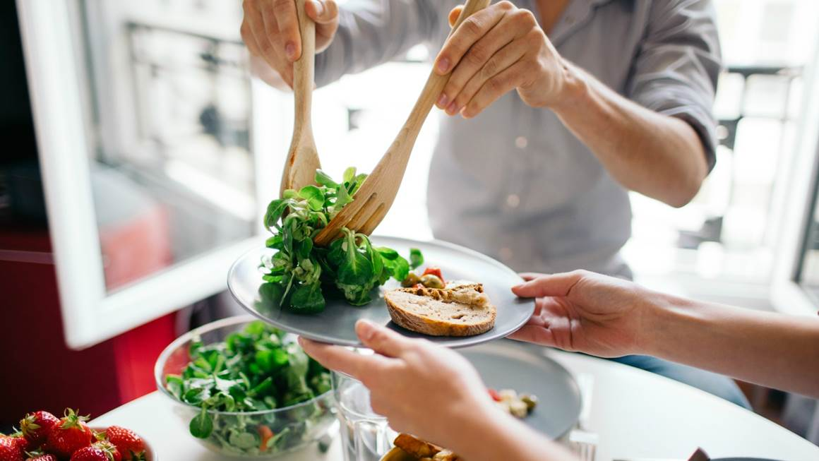 A man puts salad on a white plate with bread.