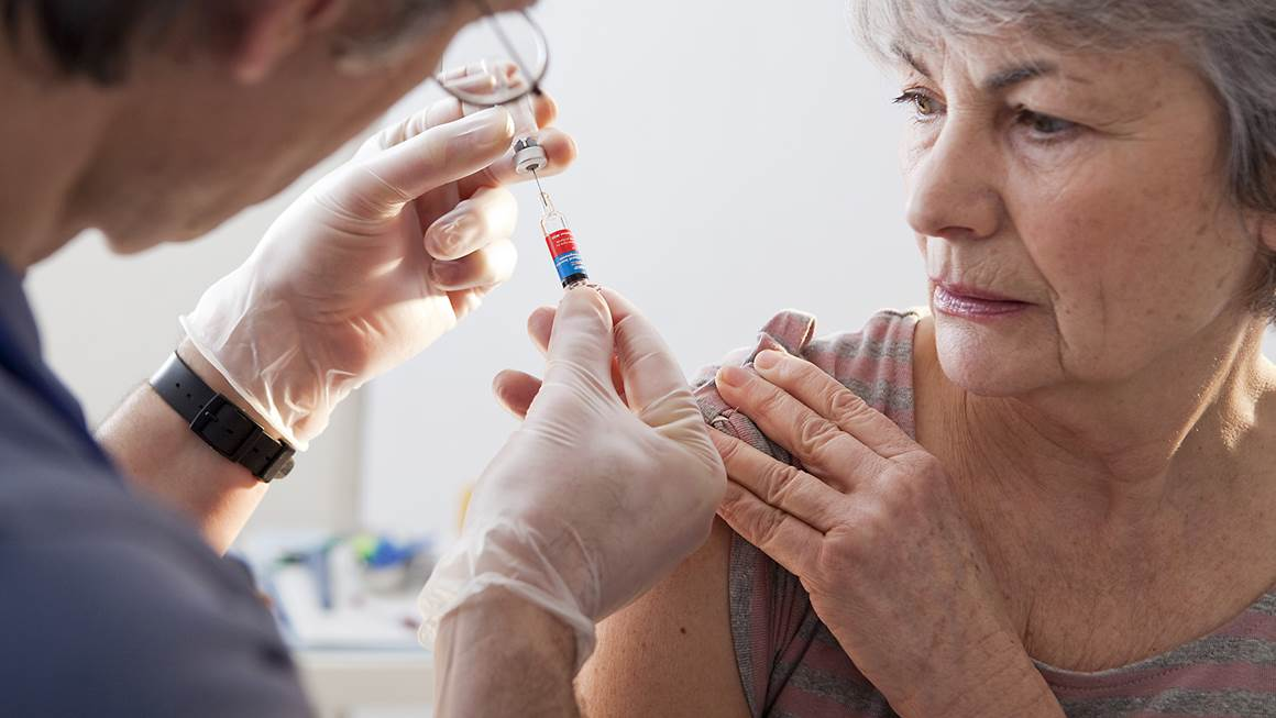 Woman lifting her sleeve to receive a flu shot from a medical professional.