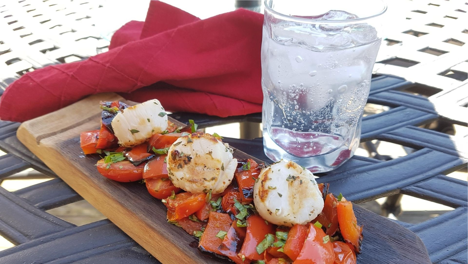 Grilled scallops with roasted tomatoes on wooden plank