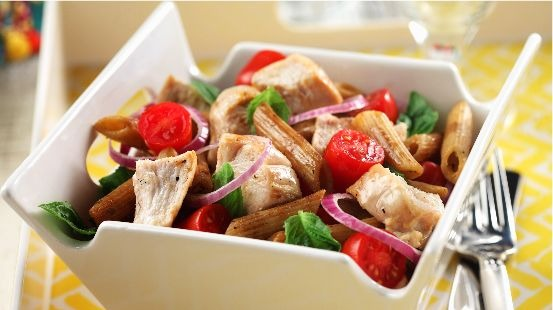 Bistro chicken pasta  salad in a square white bowl with a fork on a yellow tablecloth