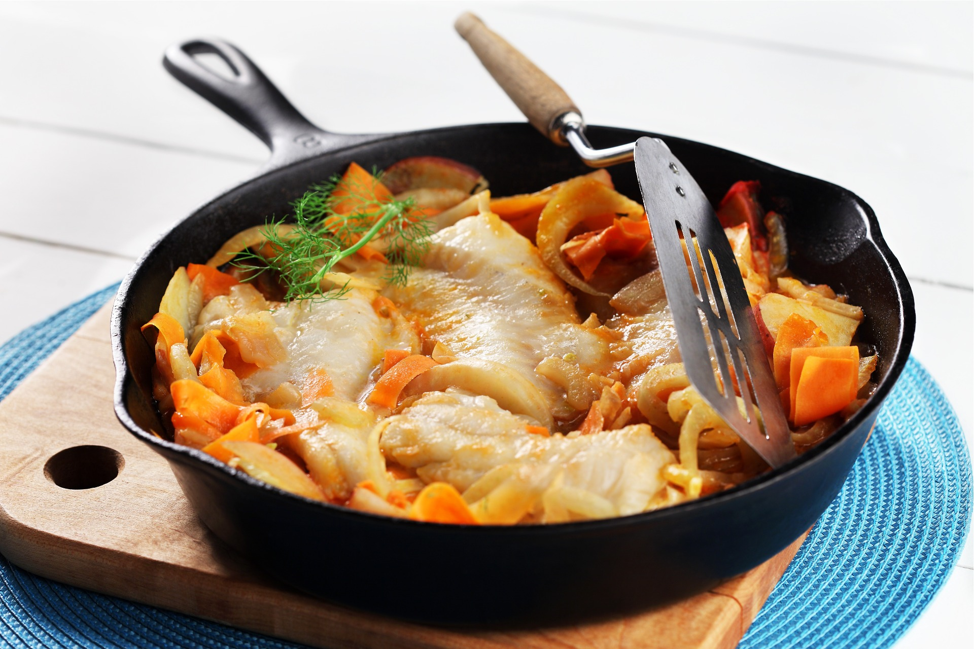 Skillet of cooked cod fillets, fennel potatoes and carrots