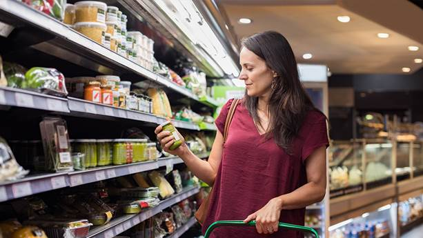 A woman looks at products on a shelf in the grocery store