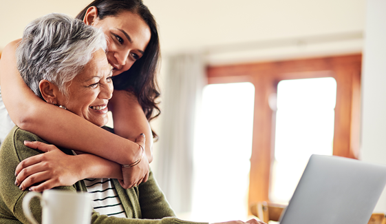 Cropped shot of an attractive young woman hugging her grandmother before helping her with her finances on a laptop