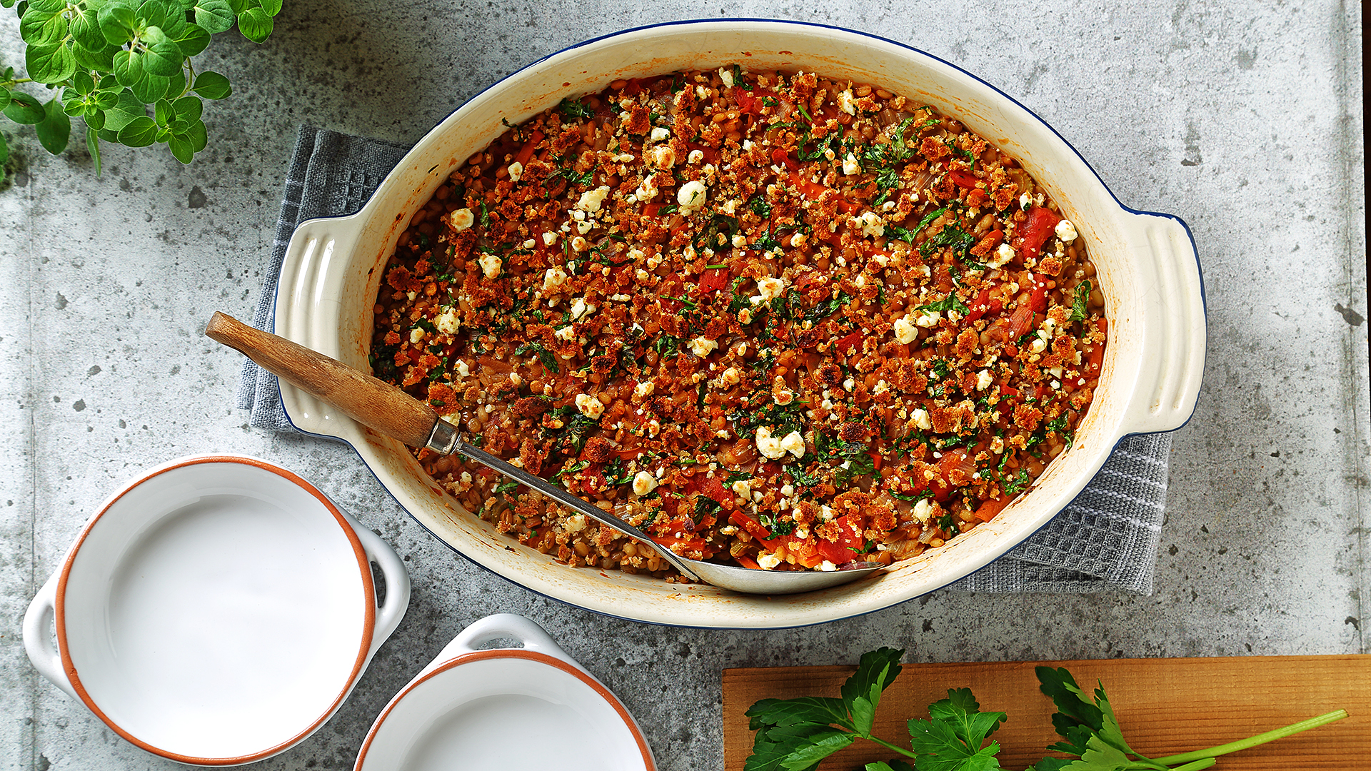 Lentil and barley oven bake casserole in ceramic serving dish with a serving spoon and two empty bowls.
