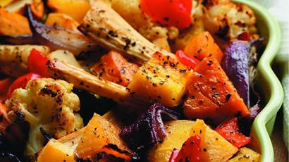 Maple roasted vegetables in a green ceramic serving bowl.