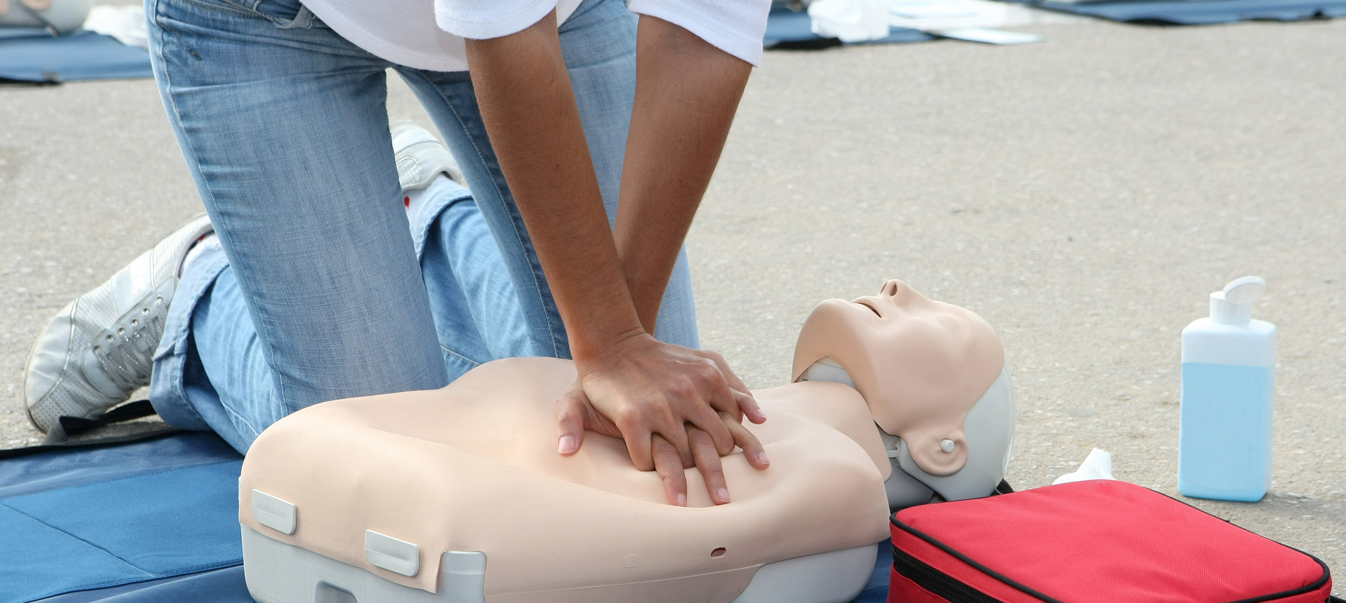 A woman performs chest compressions on a mannequin during an outside CPR training session