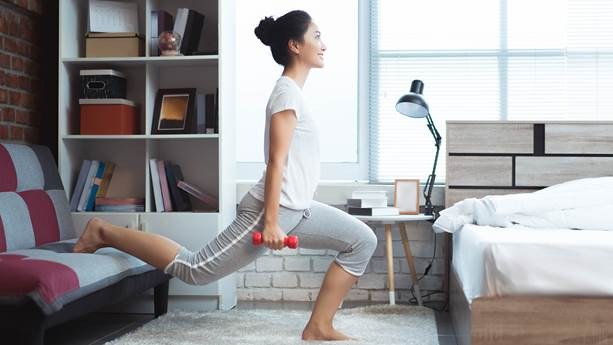 An asian woman exercising in her bedroom in the morning.