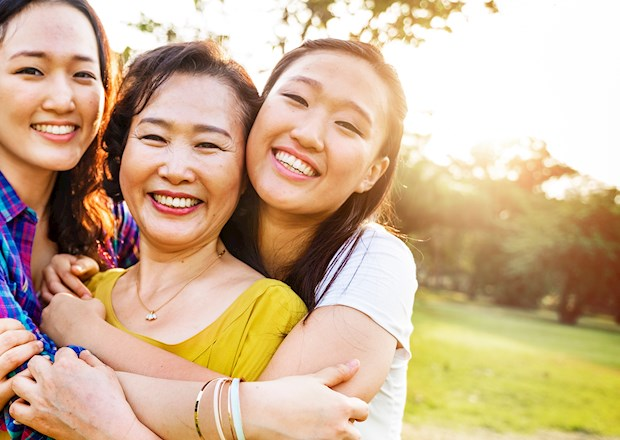 Mother, daughter and grandaughter smiling in a green field