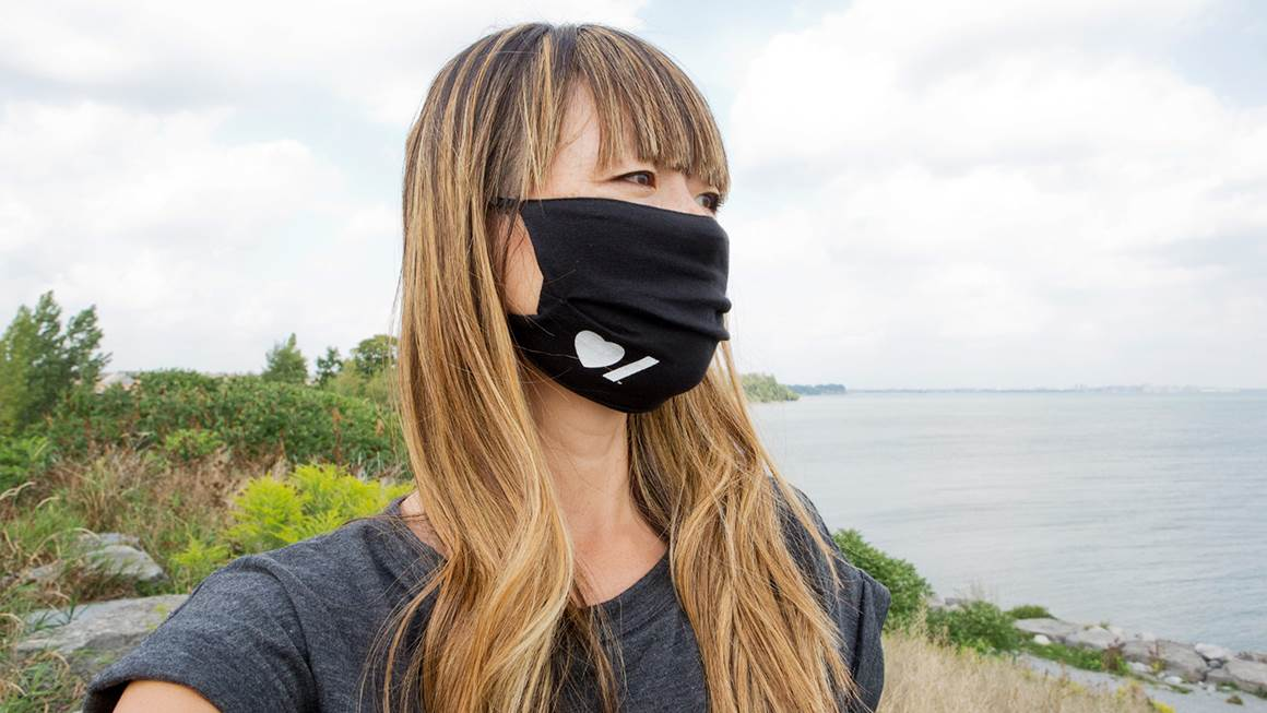 A woman takes a selfie while  wearing a black face mask with awhite Heart & Stroke logo on it