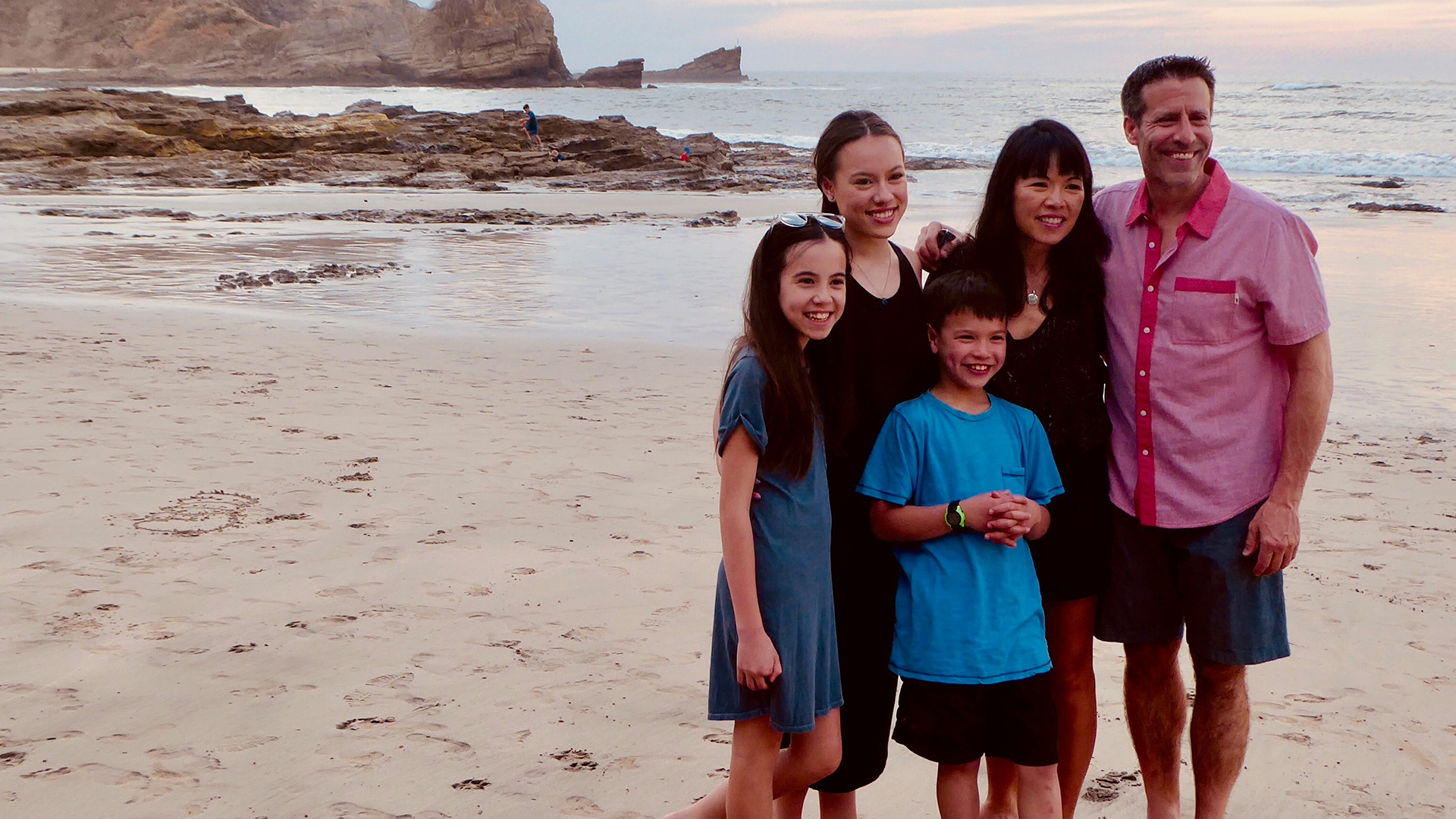 A family smiles together on a rocky beach