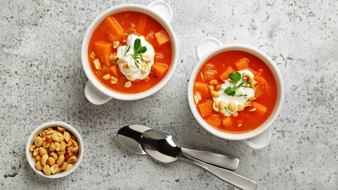 Chunky sweet potato and peanut soup in two white bowls with chopped peanuts on the side.