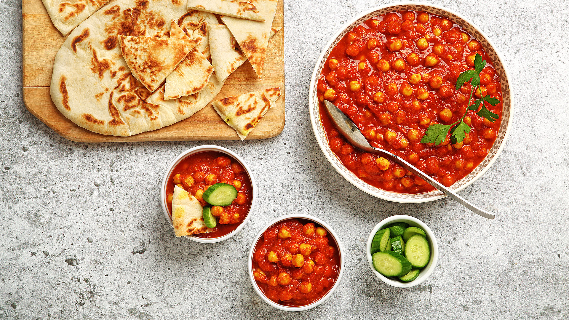 Garlic tomato chickpeas in a big serving bowl with naan on a wooden cutting board and cucumber slices in a small bowl on the side.