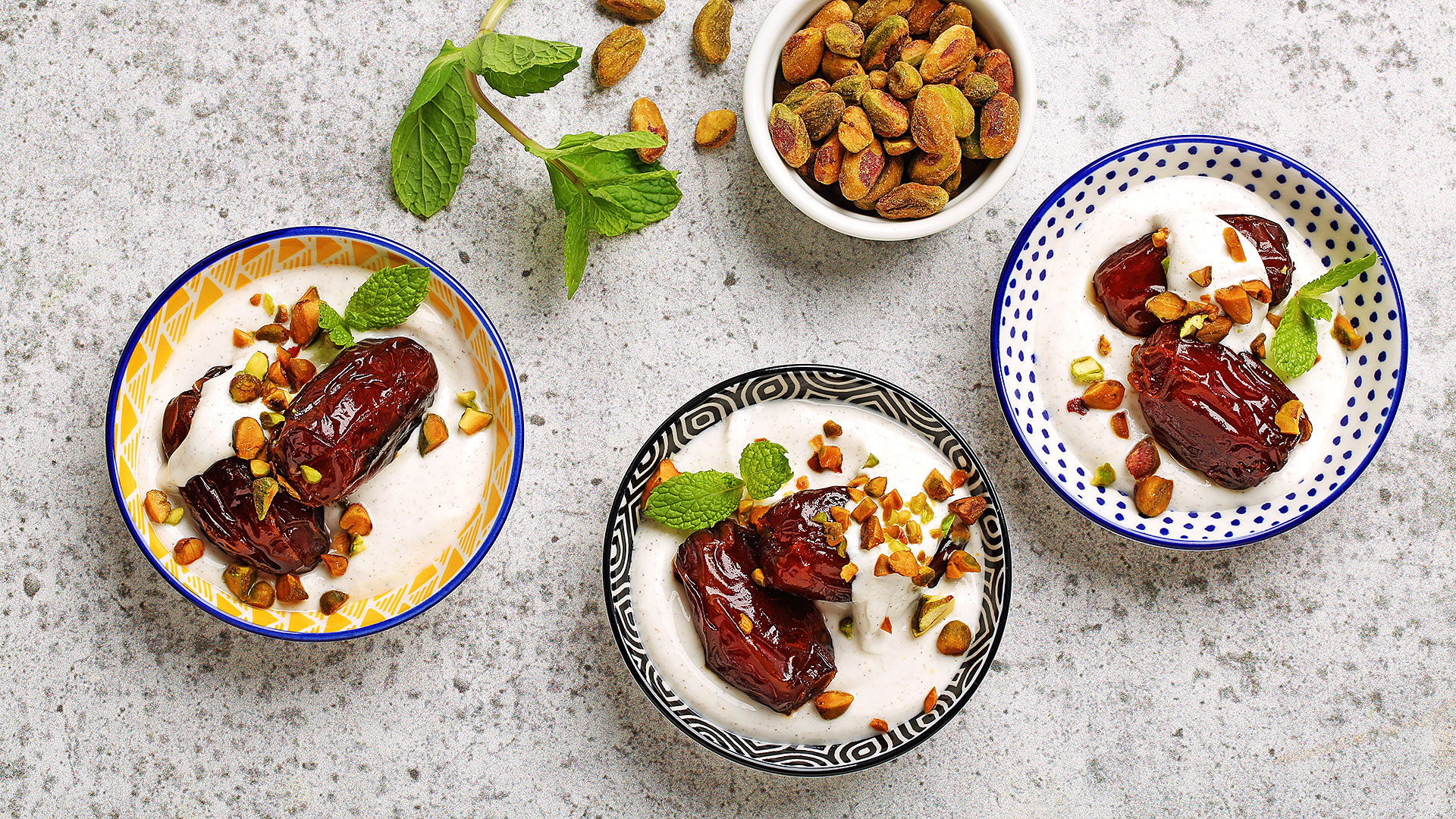 Three bowls of pan fired dates with cardamom yogurt with mint leaves and pistachios.