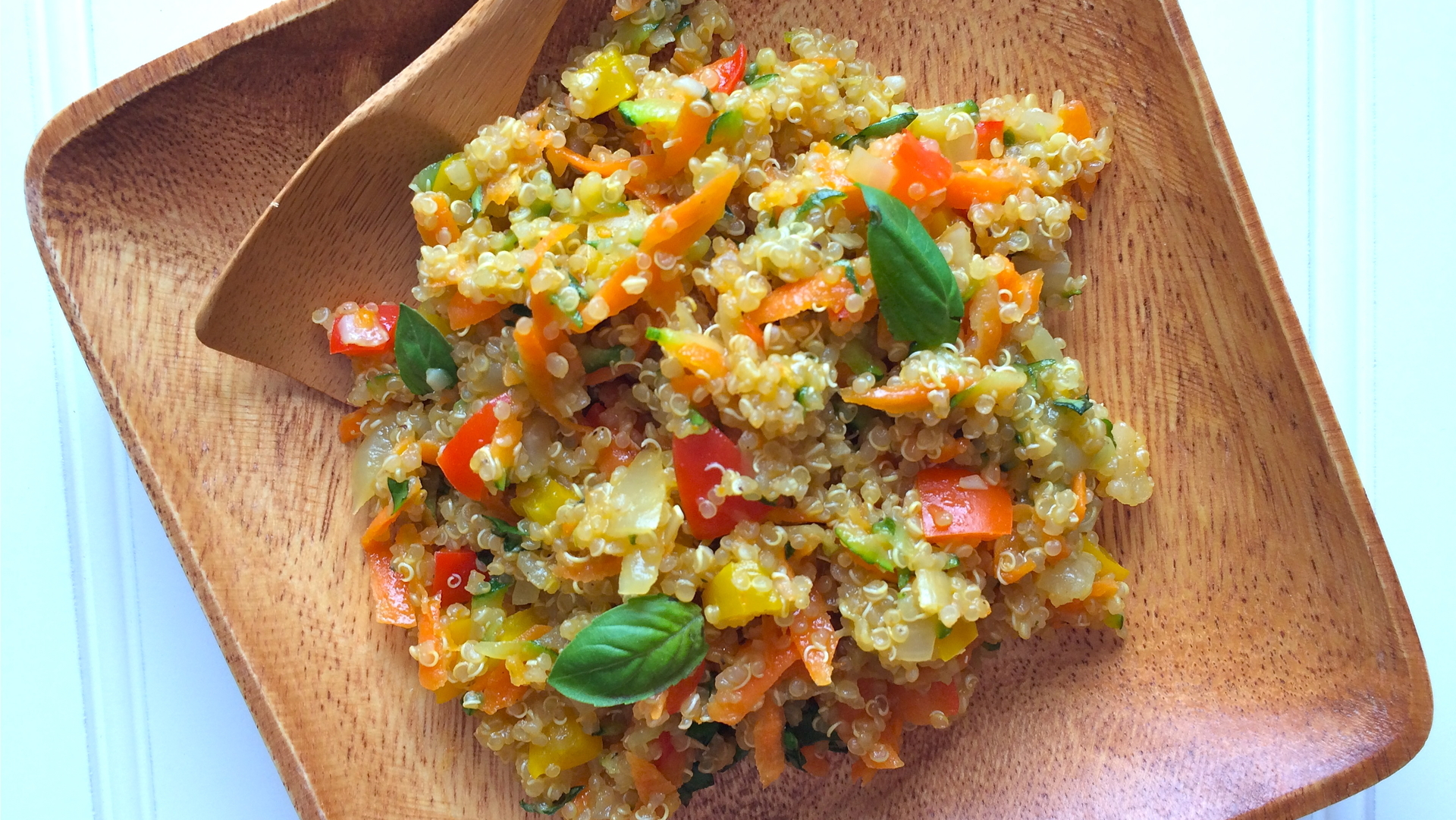 Vegetable confetti quinoa on a wooden plate and a wooden spoon