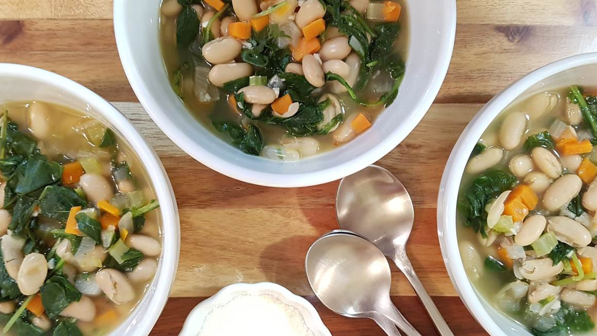 Three bowls of white bean and vegetable soup on a wooden table.
