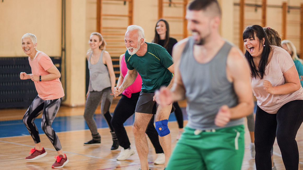 Smiling and happy group of people dancing at gym