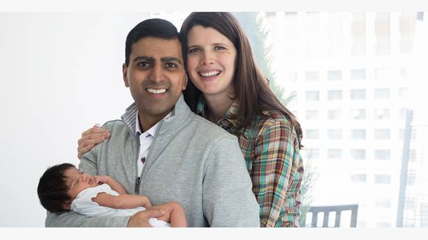 Irfhan Rawji and his wife Christine, stand close together with arms wrapped around their new born baby boy, Zain, while smiling at the camera.