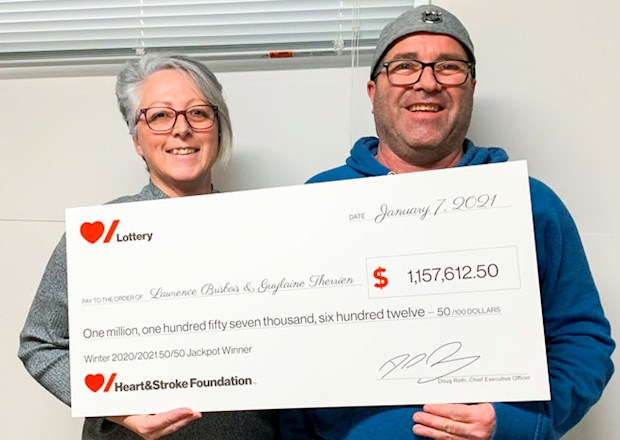 Man and woman holding large novelty cheque