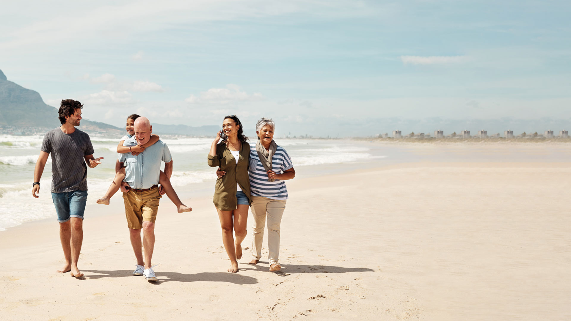 Shot of an adorable little girl having a fun day at the beach with her parents and grandparents