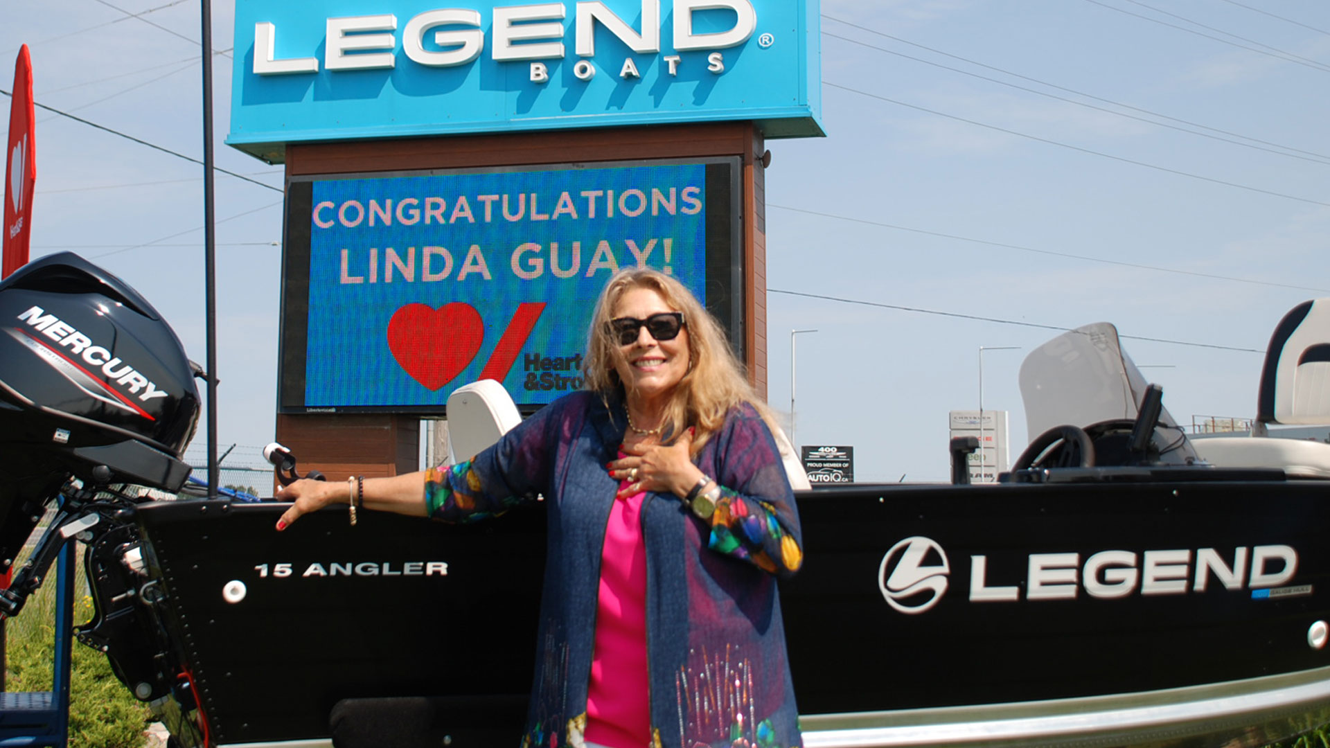 Woman standing in front of fishing boat and large Legend Boat business sign