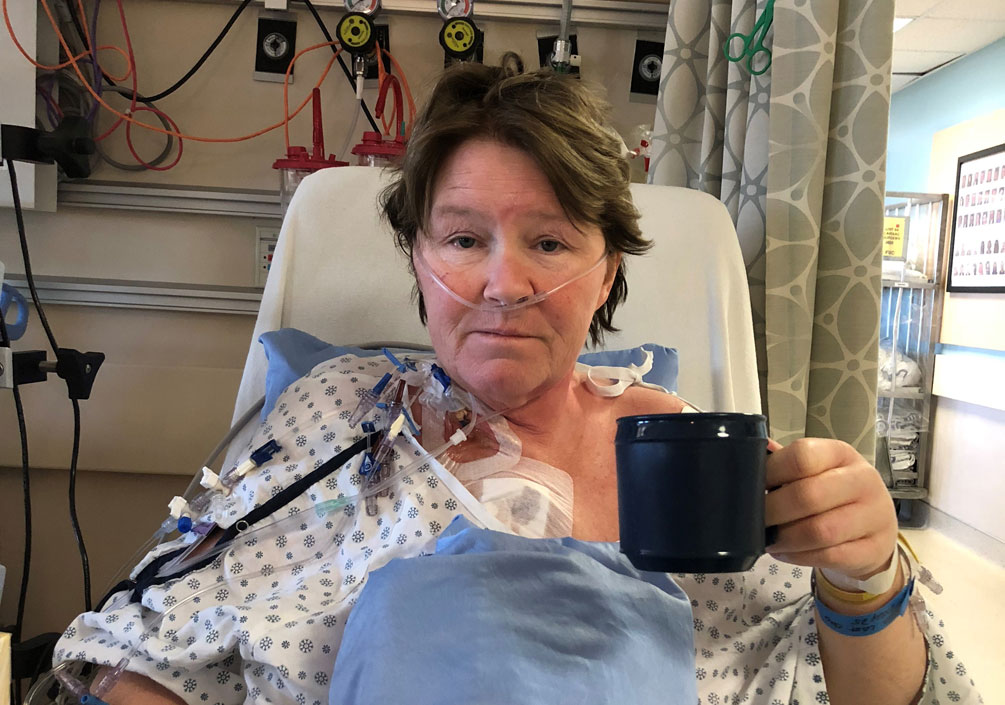 Heather Evans sitting up in a hospital bed after open-heart surgery with a mug of tea in her hand.