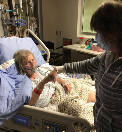 Heather giving her sister Barbara a fist bump after her open heart surgery