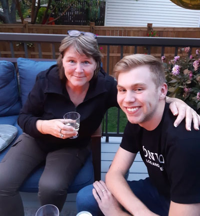 Heather with her arm around her son Skyler sitting on a porch with a glass in her hand.