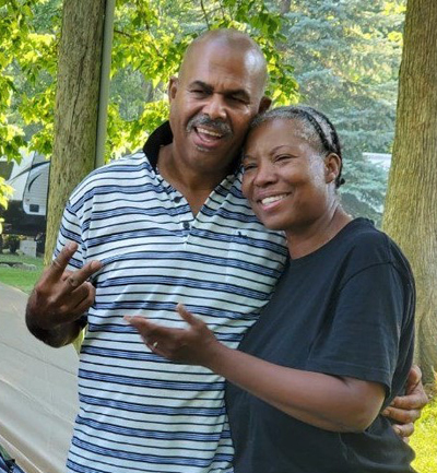 Michael and his wife Gwendolyn smiling together at  a campground.