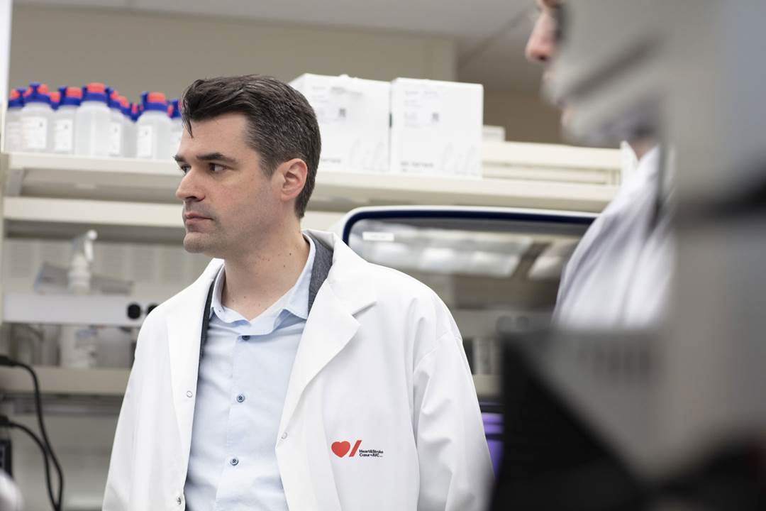 Dr. Pare in a white lab coat with the Heart & Stroke logo on it
