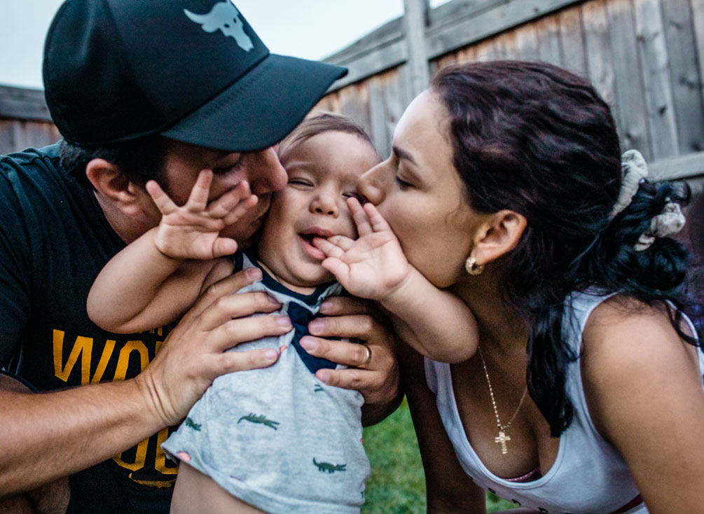 Samantha and her husband kissing their son on the cheek