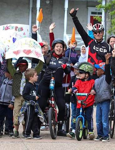 Genevieve Morel on her bike surrounded by well-wishers.