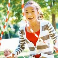 Girl jumping rope outside on a sunny day