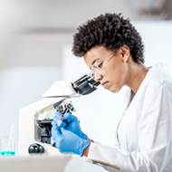 Young black woman in a lab coat looks through a microscope.